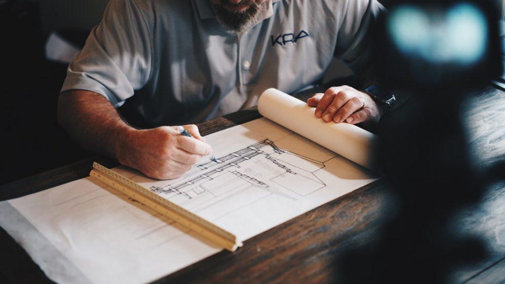 Man looking at house drawings