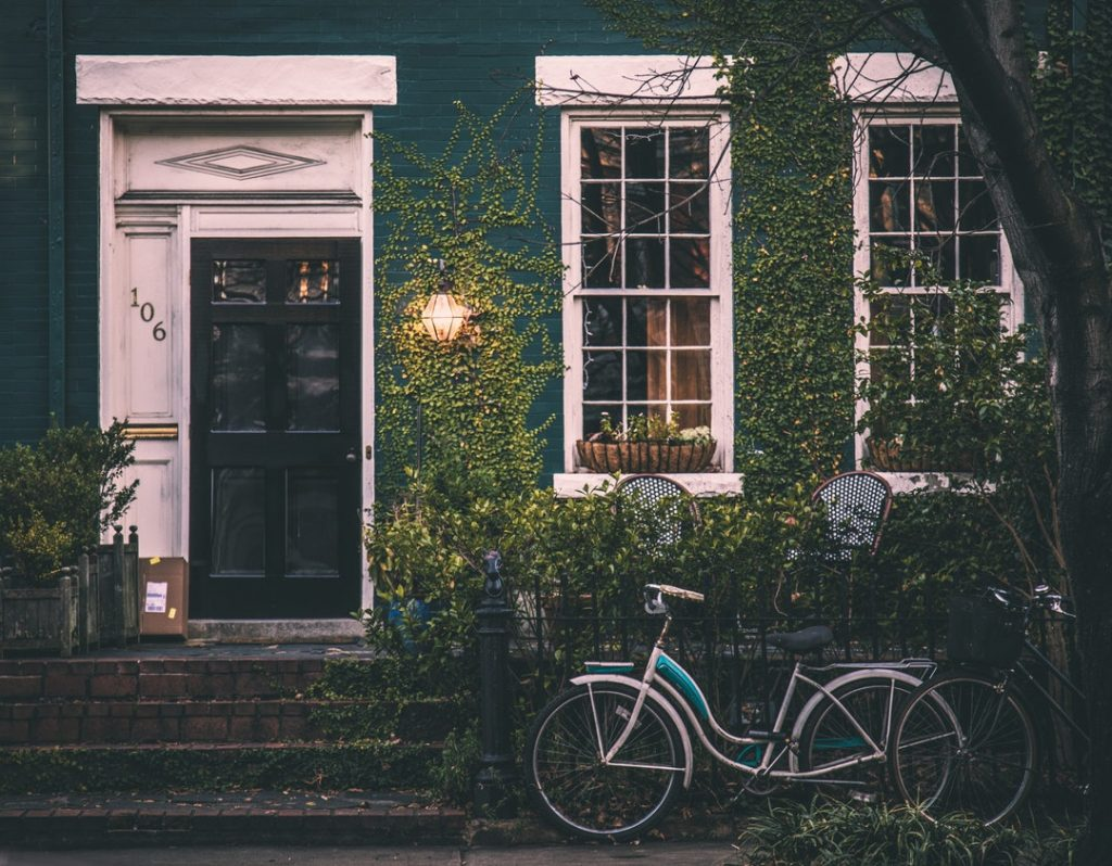 exterior of house with vines growing on it and bike sitting outside