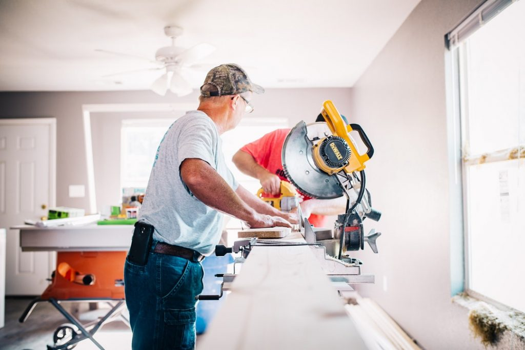 Man using saw to cut wood for renovations