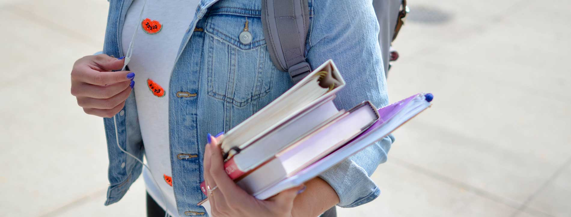 Girl with a white shirt and denim jacket, wearing a backpack and carrying a pile of books.