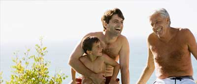A family's three generations of men, relaxing at the edge of their swimming pool. Laughing together.